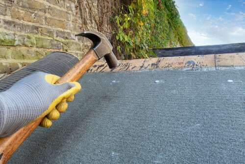 applying new felt to shed roof